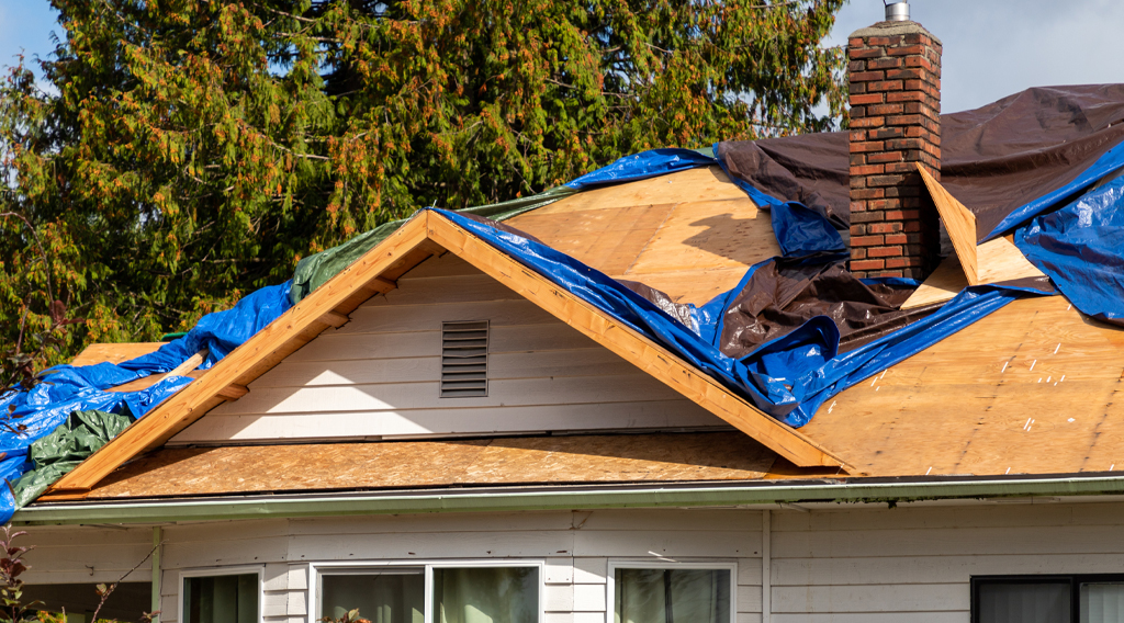 Home roof being repaired after severe weather damage
