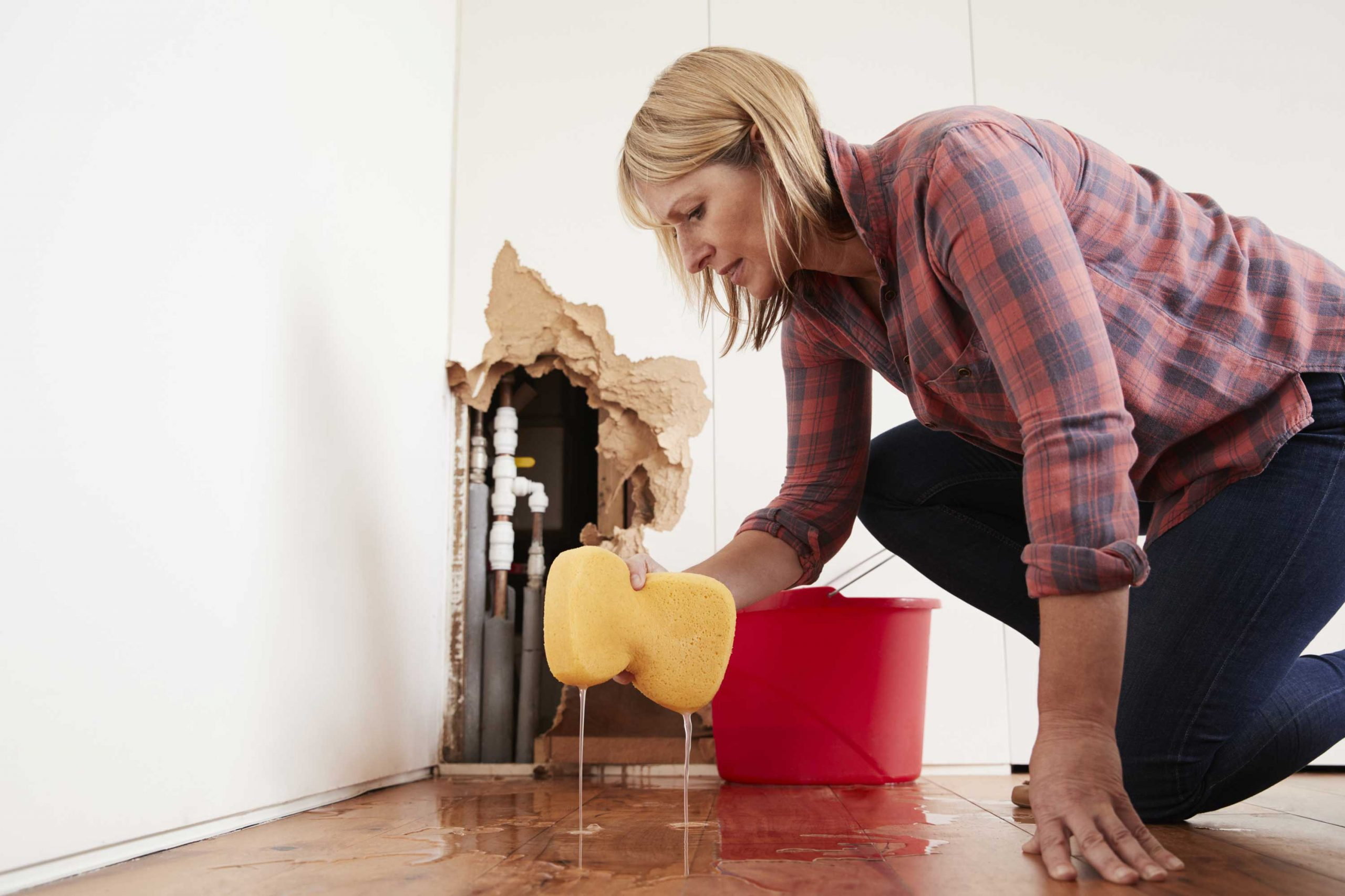 woman cleaning up water damage in her home