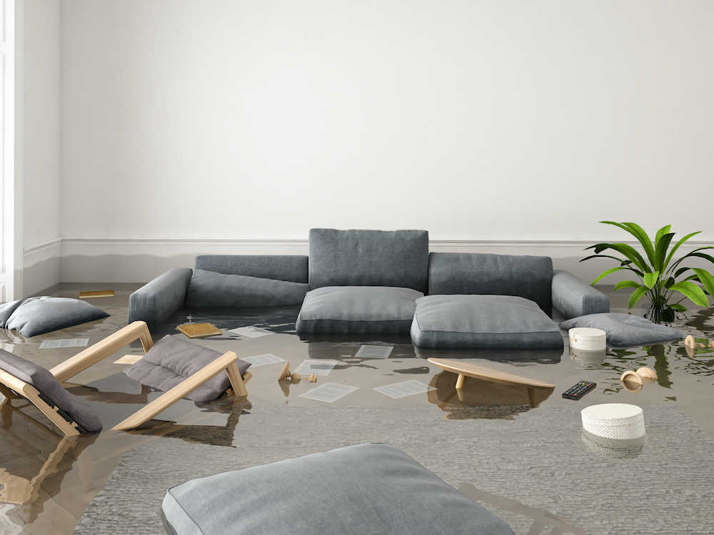 A couch and some chairs are floating in floodwaters.