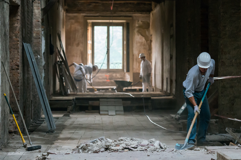 Several men from a restoration company are sweeping up debris in a home stripped to its studs