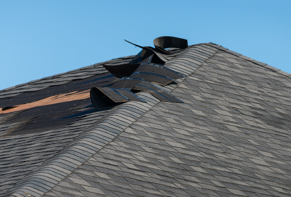 Damaged roof with loose shingles