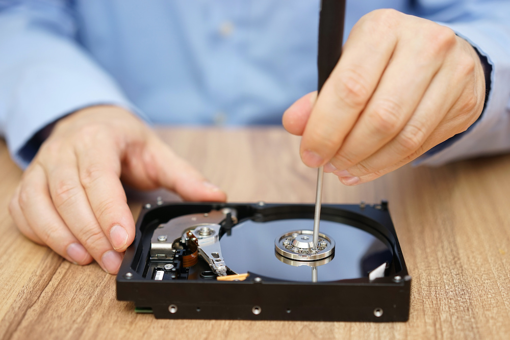 Technician performing data restoration services on hard drive