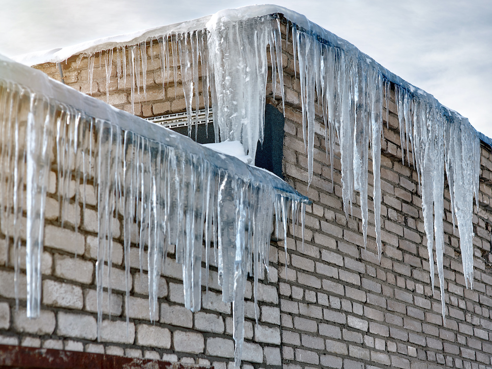 Icicles hang on the side of a building, potentially causing water damage.