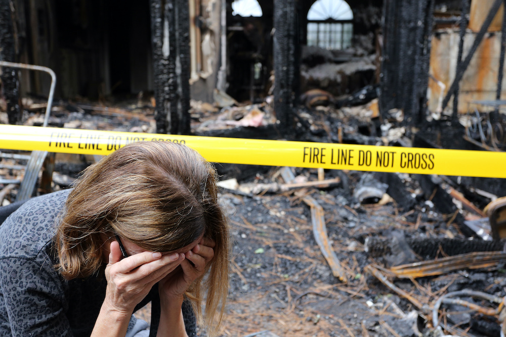 A woman has her head in her hands in front of her burned down home, needing fire damage restoration.