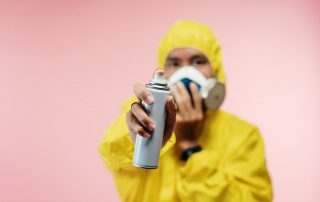 A person is spraying disinfectant while wearing a hazmat suit