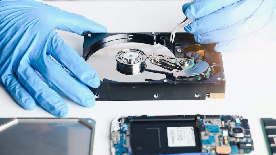A professional works on data recovery, wearing blue gloves.